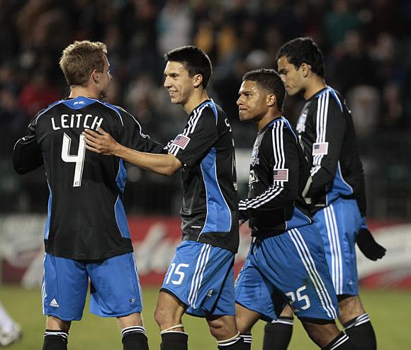 Chris Leitch, Shea Salinas, Quincy Amarikwa, and Pablo Campos celebrate Amarikwa's game-winning goal. Photo: Kelley Cox, isiphotos.net.