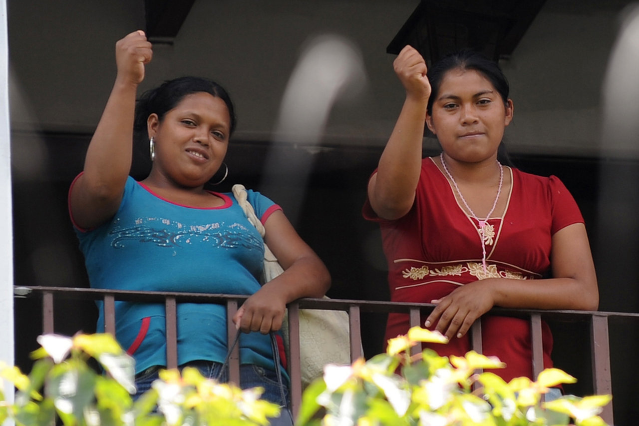 Two asylum-seekers from Honduras raise their fists from a balcony in Mexico.