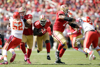 Frank Gore runs between Bruce Miller and the blocker he had engaged