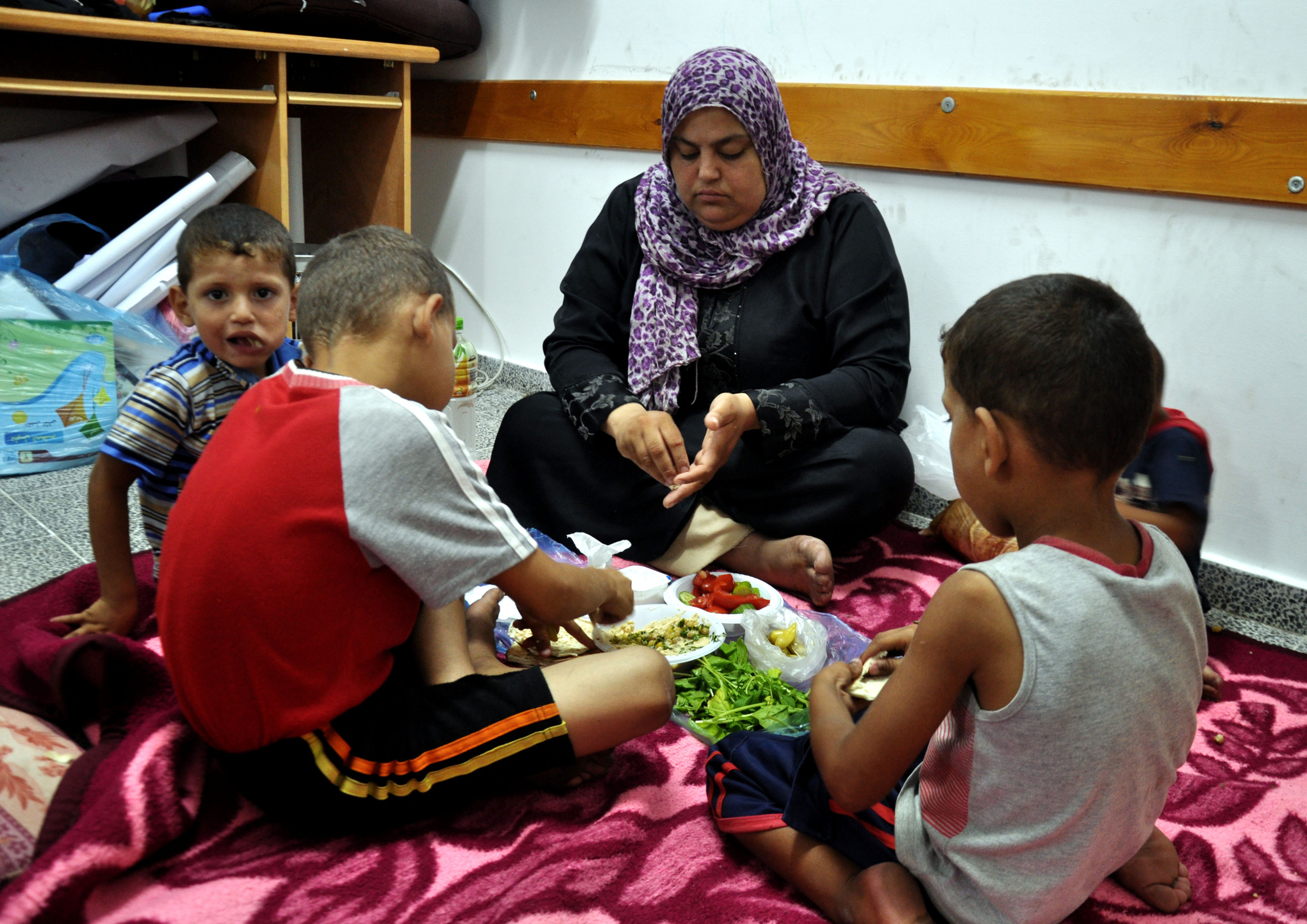 A family eats on the floor of a school turned shelter in Gaza