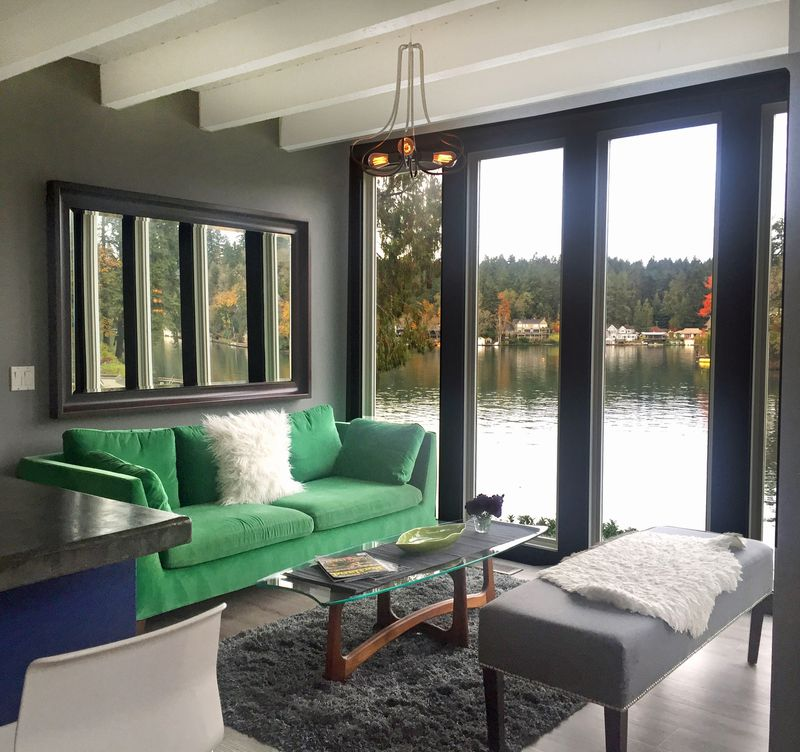 A bright green couch in a living room with dark grey walls and floor-to-ceiling windows that look out over a lake.