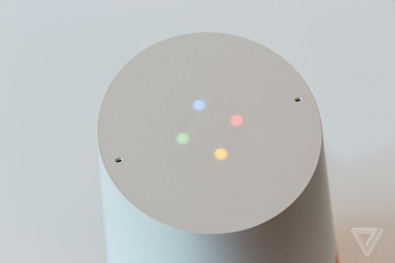 The top of the Google Home speaker, which is white with four lights in a diamond pattern: blue, red, yellow, green.