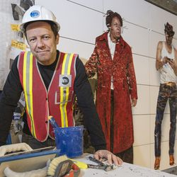 Artist Vik Muniz poses with his installation <em>Perfect Strangers </em>at the 72nd Street subway station in 2016