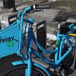 A Relay bike share bike in downtown is covered in ice.