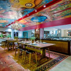 Local artist Rick Bach's modern mural over the communal table mimics the artistry of chef Hamilton Johnon's tattoos.