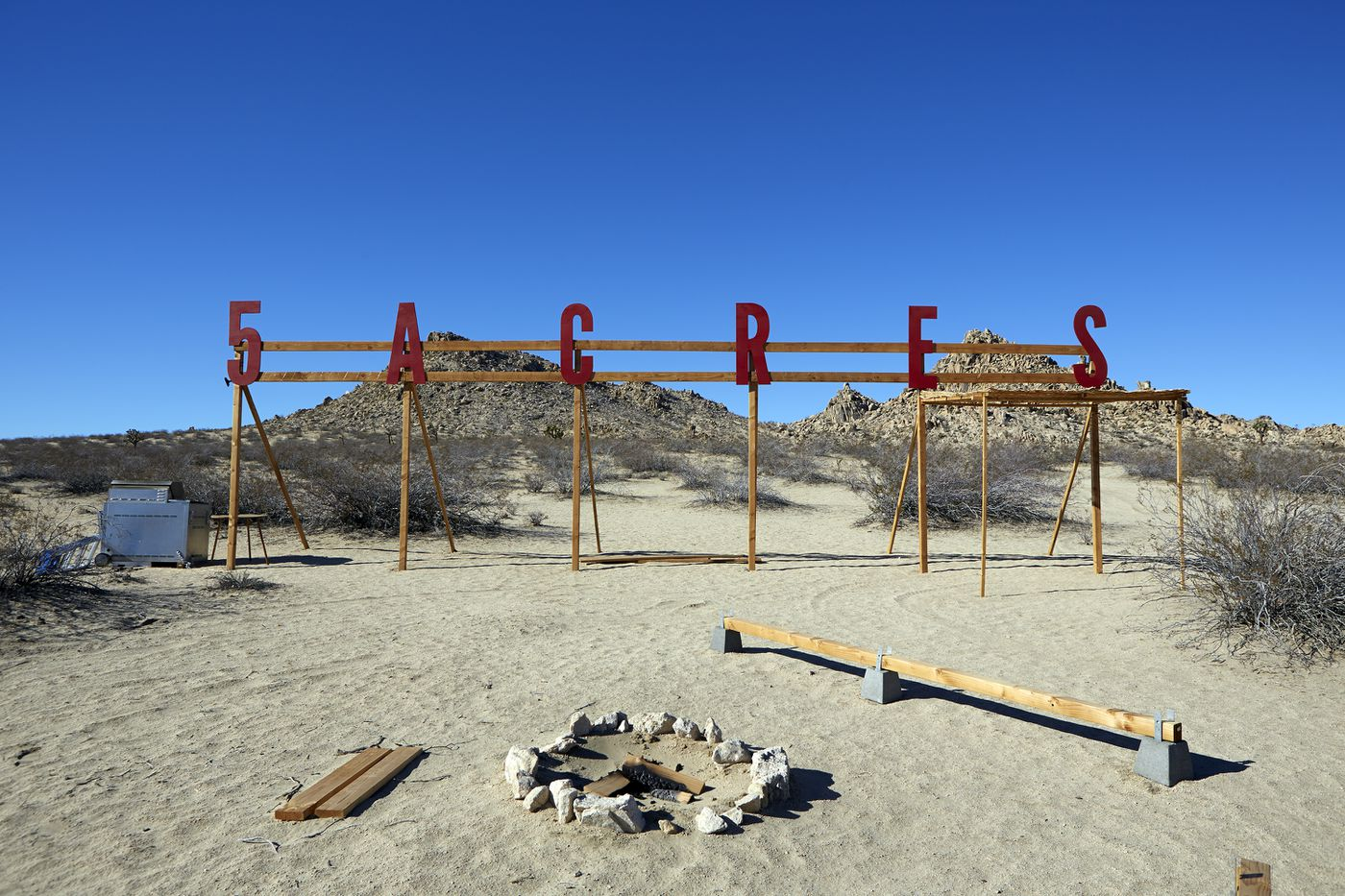 The space at 5 Acres, a sign that says 5 Acres in red, with a fire pit, surrounded by desert.