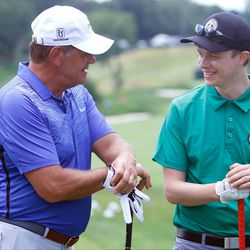 UConn women's basketball coach Geno Auriemma chats with actor Dane DeHaan at the 2017 Travelers Championship Pro-Am.<br>