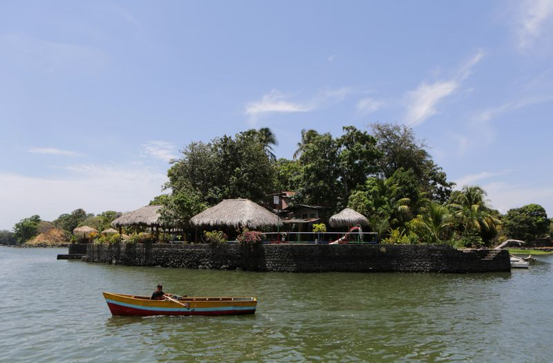 A boy rows a boat past an islet on Lake Nicaragua, also known as the Cocibolca or Granada Lake, in the Nicaraguan western city of Granada, some 45Km southeast of Managua, on April 24, 2014. (Inti Ocon/AFP/Getty Images)
