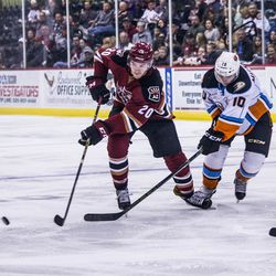 MacInnis is poke checked by a Gulls player but continues to hustle towards the puck