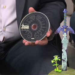 Reggie holds up the Sheikah Eye collectible coin and <em>The Legend of Zelda: Breath of the Wild Sound Selection</em>, a 24-track soundtrack CD.