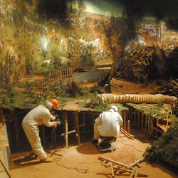 Conservationist work on the painting in Grant Park before it is rolled up for transportation.