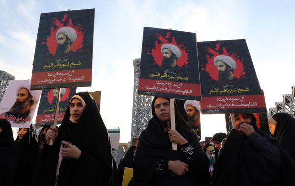 Iranian women hold posters with the image of executed Shiite cleric Nimr al-Nimr.