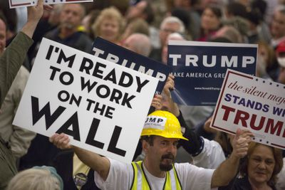 "A man at a Trump rally waves a sign that says ""I'm ready to work on the wall"""