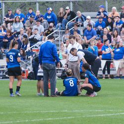 Trainers gathered around before she was carried off the field.