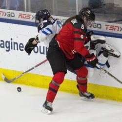 Team Canada forward Rebecca Johnston hits Team Finland defenseman Ronja Savolainen.
