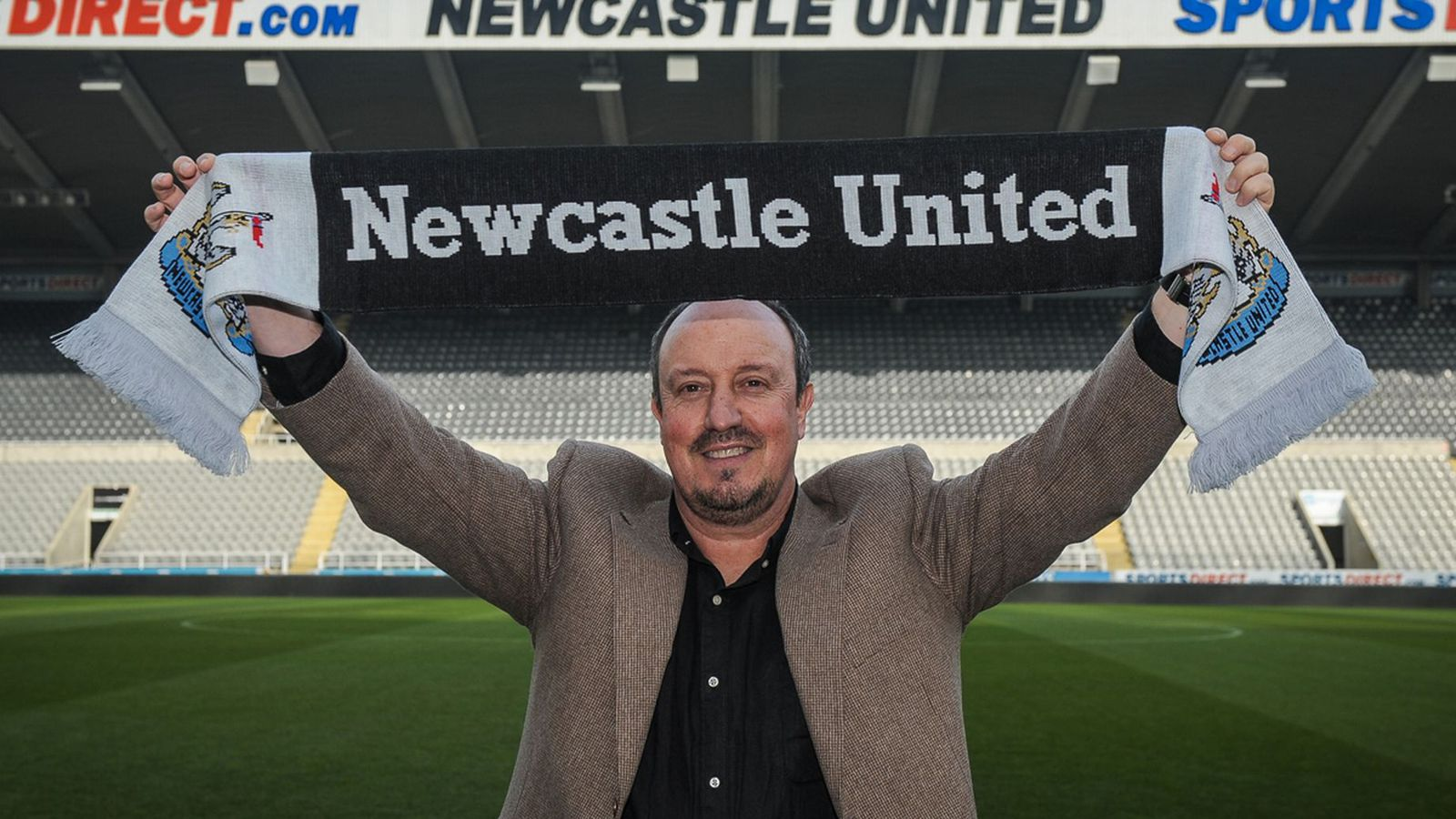 Rafael_benitez_poses_holding_a_club_scarf_signing_as_newcastle_s_new_manager.0