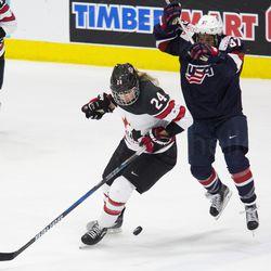 Team USA forward Amanda Pelkey and Team Canada forward Natalie Spooner look for the puck at their feet.