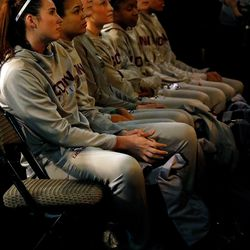 Members of the UConn women's basketball team watch as their head coach talks about winning the AP Coach of the Year award.<br>