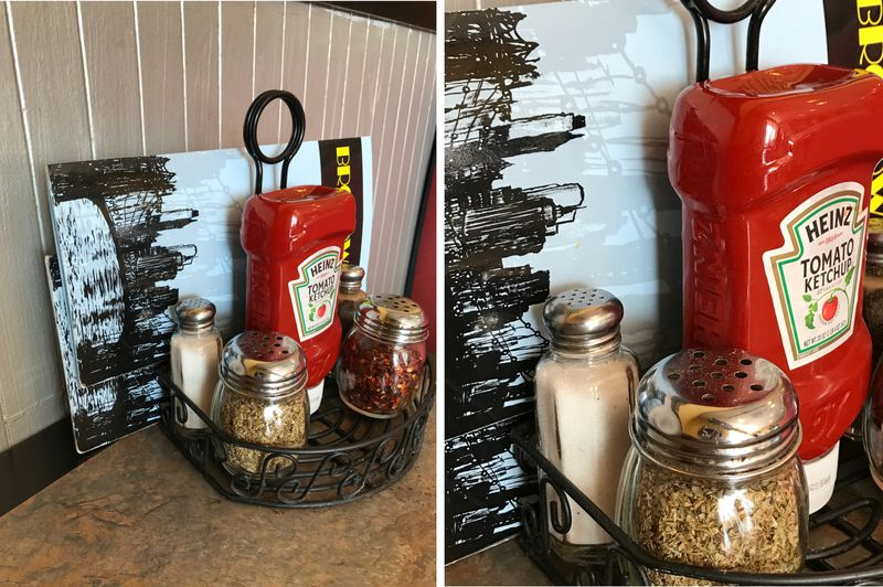 A side-by-side comparison of photos taken with the iPhone 7. On the left, a table with a caddy containing ketchup, salt, oregano and hot peppers. On the right, a closer version of the same image in which the flecks of oregano are sharply visible.
