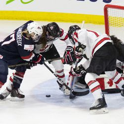 Team USA and Team Canada battle for the puck in front of the net.