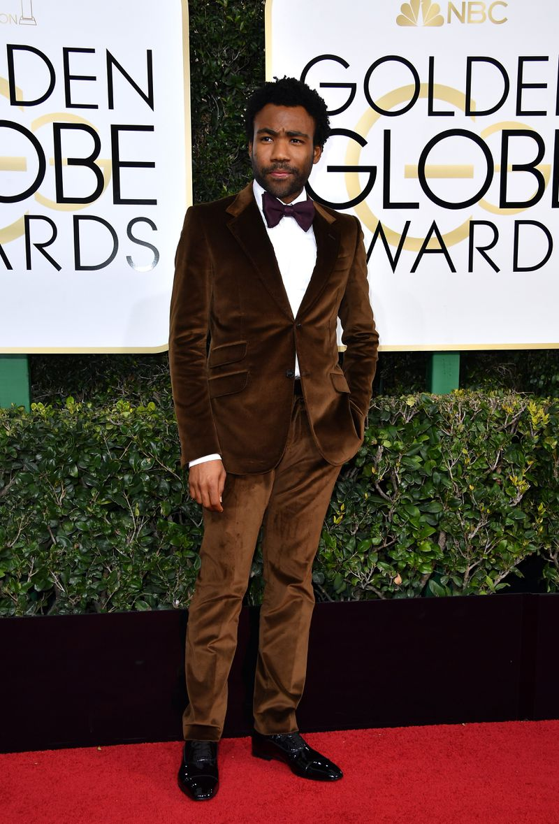 What I love: the brown velvet is such a beautifully smooth color that you could almost dive into it like melted chocolate. Also, Donald manages - at the same time - to look both like an old-school debonair gentleman, and a walking huggable teddy bear. This suit is a reminder that you don't have to go all the way to patterns or beading to explore a statement beyond the classic black tux. Plus that burgandy bow tie?! This is one of the biggest nights in Donald's career, and I just love that he is dressed for it.