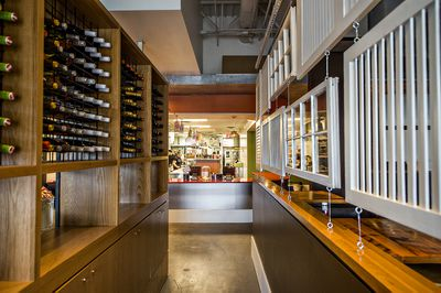 A tall wine rack and window frames greet diners upon entry.