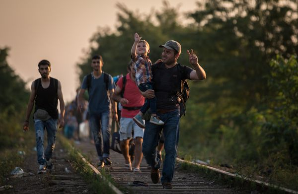 Migrants gesture as they cross the border from Serbia into Hungary (an EU country)