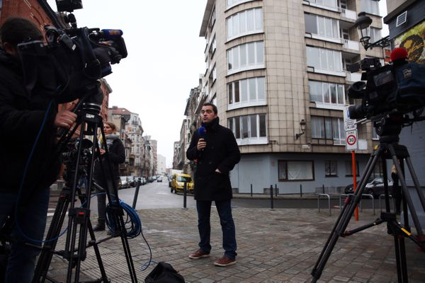 Reporters crowd outside the apartment of brothers Khalid and Brahim el-Bakraoui.