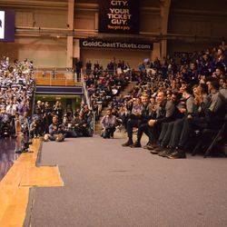 Northwestern head coach Chris Collins stands up to speak as his players encourage him.