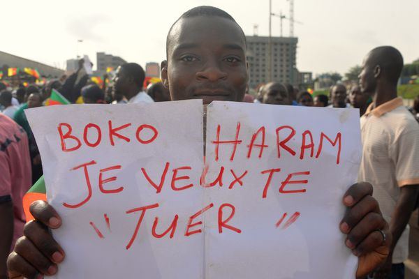 """A man holds a placard that reads """"Boko Haram, I want to kill you"""" during a demonstration against the group on February 28, 2015 in downtown Yaounde, Cameroon."""