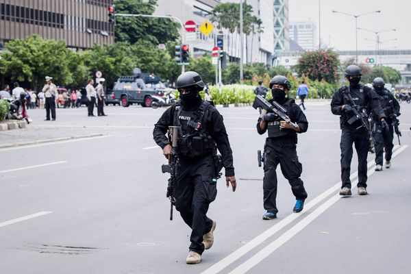 Indonesian policemen guard the blast site.