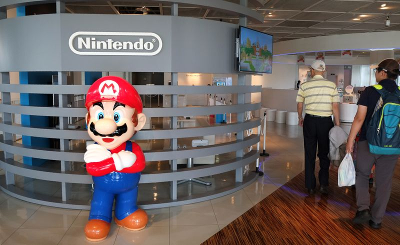 A Mario statue in front of the Nintendo logo.