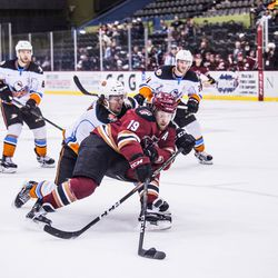 Mueller protects the puck and pushes towards the net while being pressured heavily by a Gulls' defender