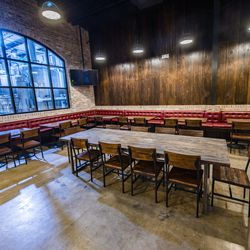 The design features wood, brick, red leather banquettes, evoking old New Orleans.
