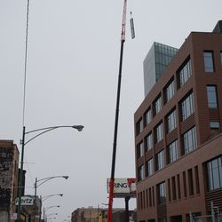 Panel being lifted to the top of the plaza building