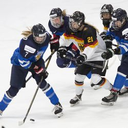 Team Germany defenseman Ronja Jenike is surrounded Team Finland players.