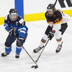 Team Finland defenseman Jenni Hiirikoski and Team Germany forward Laura Kluge battle for the puck.