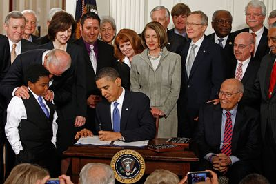 President Barack Obama signs the Affordable Care Act into law.