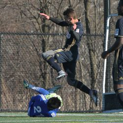 Tiger Graham leaps over goalkeeper Aaron Schwartz after he made the save