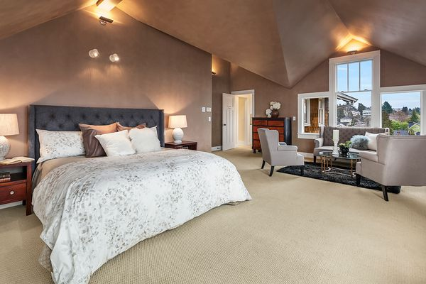 A large bedroom with vaulted ceilings and a sitting area off to the right