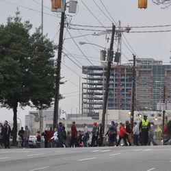 Atlanta United colors dominate as spectators cross Spring Street at North Avenue.
