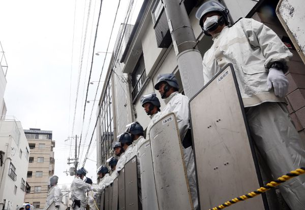 Japanese riot police stand guard outside of the headquarters of the yakuza.