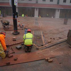 Sidewalk pavement bricks being laid down, at Clark and Addison