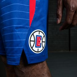 """Side view of the shorts on the Clippers' new blue """"Icon edition"""" jerseys, featuring a red stripe on the left side and a Clippers logo."""