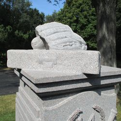 Detail of the top of the marker: a glove, ball and base