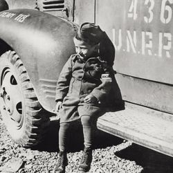 A child survivor of Buchenwald concentration camp sitting on an UNRRA (United Nations Relief and Rehabilitation Administration) truck. Germany, 1945.