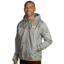 """This <a href=""""https://www.jinx.com/p/overwatch_logo_windbreaker.html""""><em>Overwatch </em>windbreaker </a>features a rubber logo patch on the top left, as well as custom zipper pulls. $59.99."""