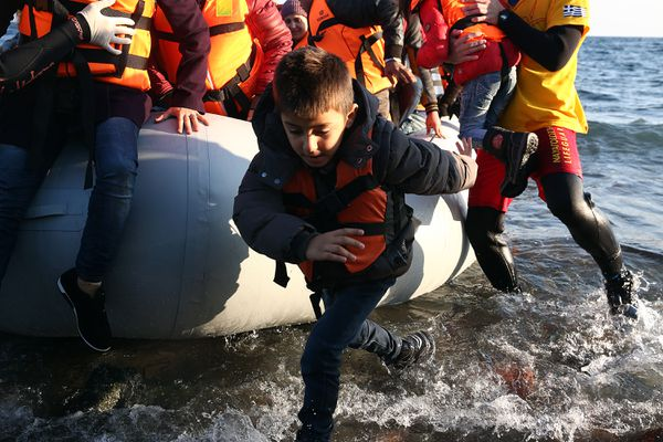 Refugees jump ashore at Lesbos, Greece.