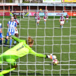 Brighton keeper Emma Byrne goes to the ground to try and stop a shot.
