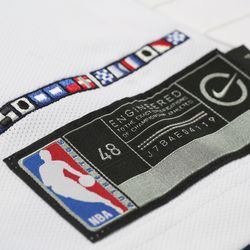 """View of the jock tag on the Clippers' new white """"Association edition"""" jersey.  The nautical flags (adapted from the nautical alphabet with Clippers colors) spell """"Clipper Nation."""""""